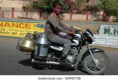 RAJASTHAN, INDIA - MARCH 14, 2006: Milkman delivering his motorcycle during the festival of holi