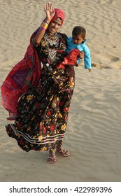 RAJASTHAN, INDIA - MARCH 20, 2006: Woman with child , waving in the Thar desert in Rajasthan
