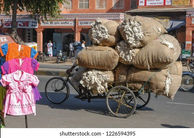Rajasthan, India - March 23, 2006: Girl clothes from a shop in the foreground and rickshaw overloaded with sacks full of wool circulating in a central street of the city of Jaipur