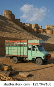 Rajasthan, India - March 25, 2006: Small cargo truck, parked in front of the walls of Jaisalmer fort, at sunset