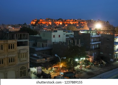 Rajasthan, India - March 25, 2006: Night view of terraces and buildings on the street of a populated Jaisalmer neighborhood, with the view of the fort illuminated in the background
