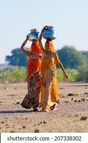 RAJASTHAN, INDIA-FEB 27: women lugging a water pot on their head on February 27, 2013 in Rajasthan, India. Due to the lack of piped water, poor tribals have to fetch water from its natural sources.