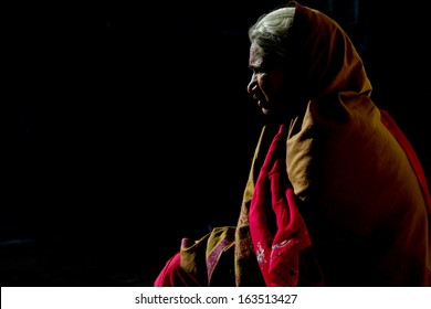 RAJASTHAN, INDIA-MARCH 14:A half silhouette of an old Rajasthani lady siting in a dark space with a little of light, Rajasthan, India, 14th of March 2011.