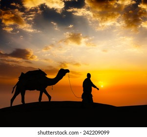 Rajasthan travel background - indian cameleer (camel driver) with camel silhouette in dunes of Thar desert on sunset. Jaisalmer, Rajasthan, India