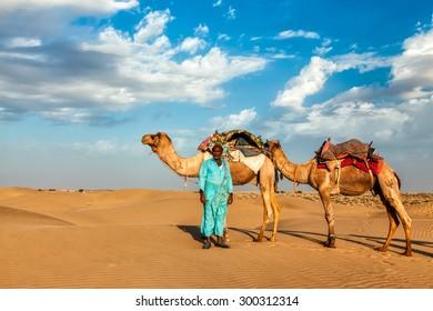 Rajasthan travel background - Indian cameleer (camel driver) with camels in dunes of Thar desert. Jaisalmer, Rajasthan, India