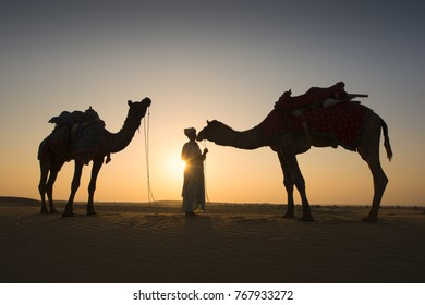 Rajasthan travel background - Indian cameleers (camel drivers) with camels silhouettes in dunes of Thar desert on sunset. Jaisalmer, Rajasthan, India