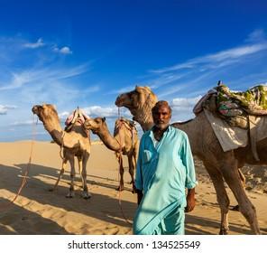 Rajasthan travel background - Indian man cameleer (camel driver) portrait with camels in dunes of Thar desert. Jaisalmer, Rajasthan, India