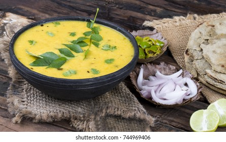 Rajasthani And Gujarati Traditional Cuisine Kadhi or Bajra Roti with Fried Chili, Onion or Lemon - Indian Vegetarian Curry Made of Buttermilk And Chick Pea Flour. Cuisine on Vintage Wooden Background