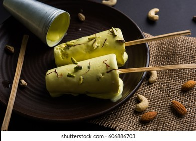 Rajasthani home made ready to eat Matka kulfi - saffron or kesariya flavoured with pistachio, cashew and almonds, selective focus
