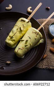 Rajasthani home made ready to eat kulfi - saffron or kesariya  flavoured with pistachio, cashew and almonds, selective focus