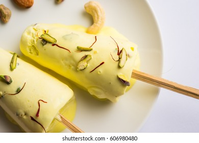 Rajasthani home made ready to eat Matka or Rajwadi or Rajwari kulfi - saffron or kesariya flavoured with pistachio, cashew and almonds, selective focus