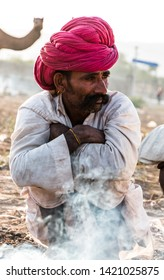 Rajasthani man getting warn himself with red turban and white dress during the winter morning of Pushkar camel fair : Pushkar, Rajasthan/India - Oct 2017