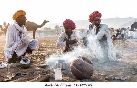 Rajasthani people getting warn themselves and having cigarette with red turban and white dress during the winter morning of Pushkar camel fair : Pushkar, Rajasthan/India - Oct 2017