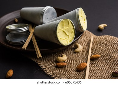 Rajasthani Shahi Kulfi is a popular frozen dairy dessert and known as Indian Ice Cream, Saffron flavoured with dry fruits. Served in a plate with Aluminium Moulds and Bamboo sticks, selective focus