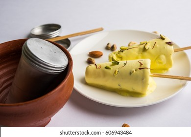 Rajasthani Shahi Kulfi is a popular frozen dairy dessert and known as Indian Ice Cream, Saffron flavoured with dry fruits. Served in a plate over moody background, selective focus