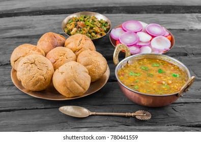 Rajasthani Traditional Cuisine Dal Baati Also Know as Dal Bati or Daal Baati Churma on Wooden Background. It is popular in Rajasthan, Uttar Pradesh and Madhya Pradesh.