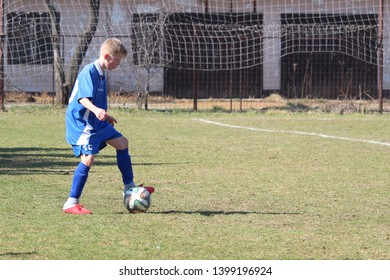 RAJEC, SLOVAKIA - MARCH 23, 2019: Player with the ball during league kids football match between teams FK Rajec and FK Slavia Staskov in category U15. FK Slavia Staskov (in red) won this match 0:4.
