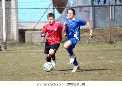 RAJEC, SLOVAKIA - MARCH 23, 2019: Tackle for ball during league kids football match between teams FK Rajec and FK Slavia Staskov in category U15. FK Slavia Staskov (in red) won this match 0:4.