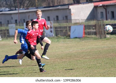 RAJEC, SLOVAKIA - MARCH 23, 2019: Tackle for the ball during league kids football match between teams FK Rajec and FK Slavia Staskov in category U15. FK Slavia Staskov (in red) won this match 0:4.
