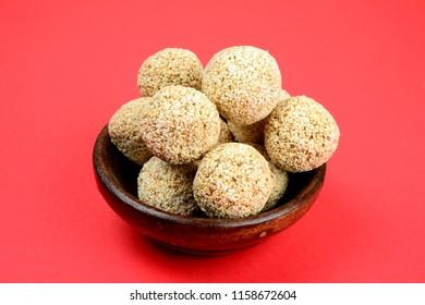 Rajgira Laddo, Cholai ke Laddo or Amaranth laddoo in wooden bowl on Red Background