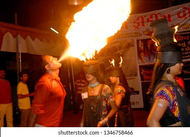 Rajkot, Gujarat; india : Sep. 27; 2009 - Festival Navratri Durga Pooja Dandia raas Fire on Garba and Round Ring on Head and girl Covered her Eyes with Black Cloth a Man Blowing Fire.
