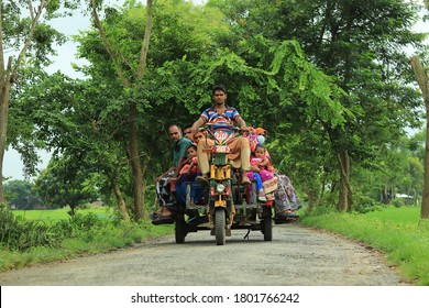 Rajshahi, Bangladesh - August 17, 2020: A few peoples riding on a van in the village, Local transport system in Bangladesh village, Risky transport system in Bangladesh village