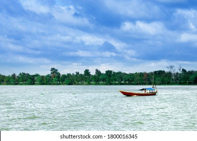 Rajshahi, Bangladesh - Aygust 17 2020: The boatman driving a boat over the river/ lake in a cloudy day in a village.