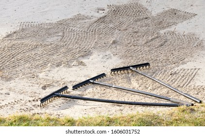 Rake in sand bunker at golf links course green for golfers