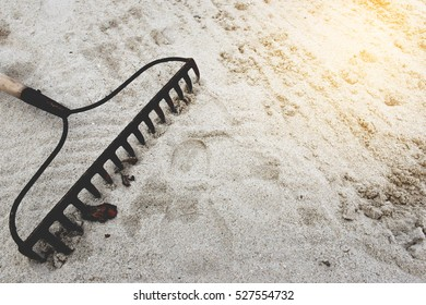 rake in sand with flare light