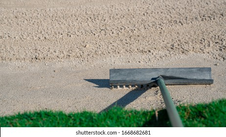 Rake in the sand trap on a golf course course