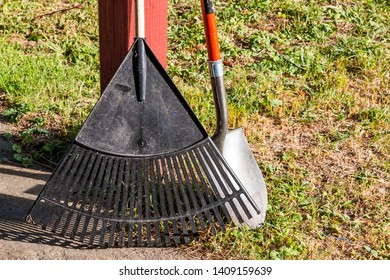 A rake and shovel rest on a wooden post near a brown and green lawn.