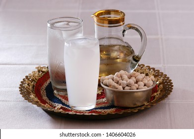 raki service on a tray, a glass of icy water, raki in glass and carafe, roasted chickpeas