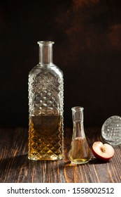 Rakia or rakija traditional Balkan fruit brandy. Plum brandy slivovica in a glass which is called cokanj and bottle on a wooden table and dark background. Vertical. Copyspace