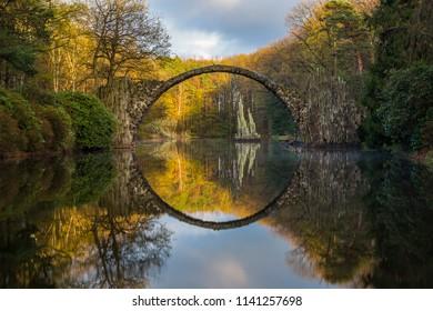 Rakotz Bridge (Rakotzbrucke, Devil's Bridge) in Kromlau, Saxony, Germany. Reflection of the bridge in the water create a full circle