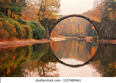 Rakotz Bridge (Rakotzbrucke, Devil's Bridge) in Kromlau, Saxony, Germany. Colorful autumn, reflection of the bridge in the water create a full circle.Unusual and interesting places in Germany.