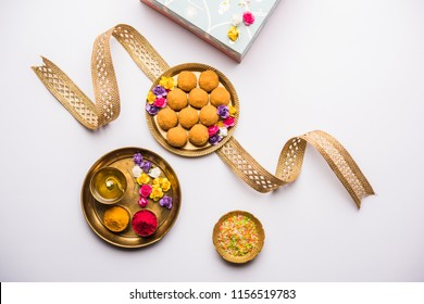 Raksha bandhan Festival : conceptual Rakhi made using plate full of Bundi Laddu sweet with band and Pooja Thali. A traditional Indian wrist band which is a symbol of love between Brothers and Sisters