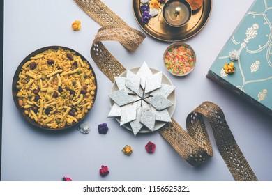 Raksha bandhan Festival greetings: conceptual Rakhi made using a plate full of Kaju Katli Barfi/Burfi and fancy band and pooja Thali. selective focus