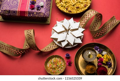 Raksha bandhan Festival greetings: conceptual Rakhi made using a plate full of Kaju Katli Barfi/Burfi and fancy band and pooja Thali. selective focus