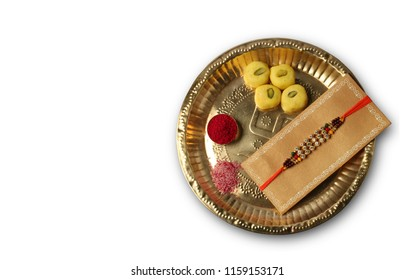 Raksha Bandhan or rakshabandhan festival showing designer Rakhi with Pooja Thali, Sweets, gift arranged over white background. Selective focus. Designer Rakhi