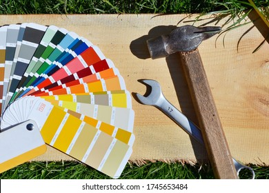 RAL color palette and construction tools laid out on a wooden board on a background of green lawn