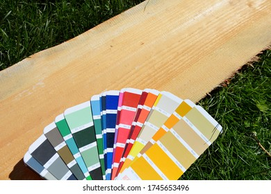 RAL color palette spread out on a wooden board on a background of green lawn