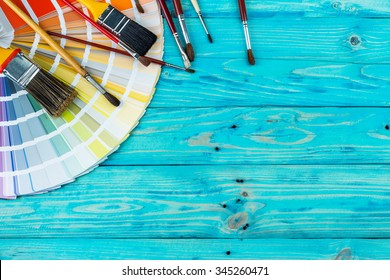 RAL colour standard Samples with brushes of different sizes on a blue wooden background. Creative design and construction of redecoration