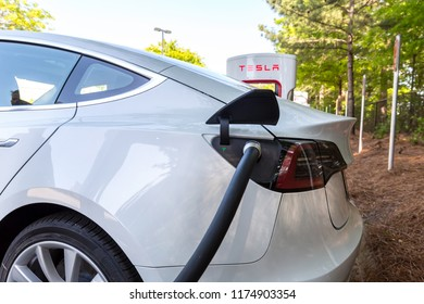 RALEIGH, NC - APRIL 30, 2018: Charging a Tesla Model 3 at a Tesla Supercharger station in Raleigh, NC. Tesla motors develops network of the charging stations across the US and the world.