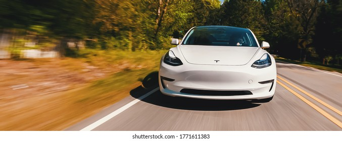 RALEIGH, NC USA, APRIL 17, 2020: A new Tesla Model 3 all electric vehicle driving down a country road