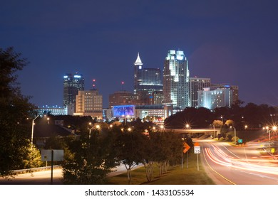 Raleigh, NC / USA - circa 2016: Skyline of Raleigh, North Carolina at dusk with the roadway in the foreground.
