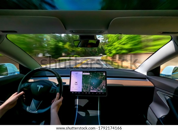 RALEIGH, NC USA, MAY 09, 2020: Person driving a new Tesla Model 3