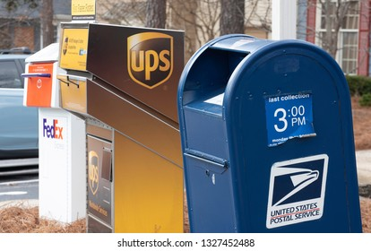 Raleigh, NC/United States- 02/13/2019: Drop off boxes for different couriers including the USPS, FedEx, and UPS.