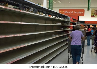 Raleigh, NC/United States- 09/11/2018:  A shopper walks past an empty bread aisle ahead of hurricane Florence.