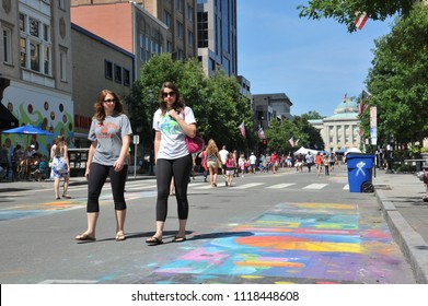 Raleigh, NC/US- 09/21/2013: Two college girls walk past chalk art along Fayetteville street.