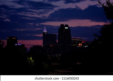 RALEIGH, NORTH CAROLINA - JUNE 6, 2018: View of the skyline of downtown Raleigh, or City of Oaks, silhouetted by the partly cloudy morning twilight sky.